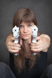 Young serious woman aims from two pistols Stock Image