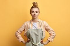 Young serious woman in apron posing with arms on hips stock photo