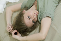 Young serious  woman in bed Stock Images
