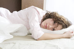 Young serious  woman in bed Stock Photos