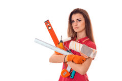 Young serious woman with dark hair in uniforl makes renovations with tools in her hands isolated on white background Royalty Free Stock Photos