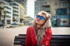 Young serious woman in elegant red dress and sunglass sits on on the bench. On the background of cityscape. Pensive blonde girl is looking to the sky in warm Stock Image