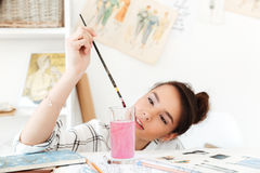 Young serious woman fashion illustrator drawing. Image of young serious woman fashion illustrator sitting at the table and drawing. Looking aside Royalty Free Stock Images