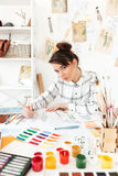 Young serious woman fashion illustrator drawing. Image of young serious woman fashion illustrator sitting at the table and drawing. Looking at camera Royalty Free Stock Photography
