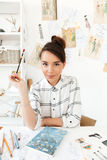 Young serious woman fashion illustrator. Image of young serious woman fashion illustrator sitting at the table and drawing. Looking at camera Royalty Free Stock Photo