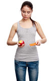 Young serious woman holding a pill in one hand and an apple in t Stock Images