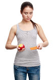 Young serious woman holding a pill in one hand and an apple in t Royalty Free Stock Photos