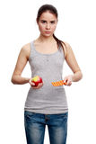 Young serious woman holding a pill in one hand and an apple in t. Choise. Young serious woman holding a pill in one hand and an apple in the other, isolated on Stock Image