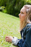 Young serious woman looking ahead while lying on the grass Royalty Free Stock Photos