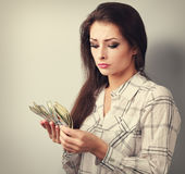 Young serious woman looking and counting dollars and thinking ho Stock Photography