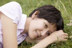 Young serious woman in lying on grass Stock Photography