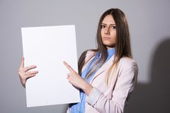 Young serious woman pointing at white sheet Royalty Free Stock Image
