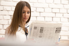Young serious woman read the latest news in the newspaper Royalty Free Stock Image