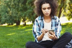 Happy young woman using smartphone in park stock photos