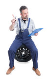 Young serious worker with checklist making refusal gesture. And sitting on wheel isolated on white background Royalty Free Stock Images