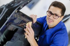 Young service mechanic cleaning automobile car door. Mechanic royalty free stock image