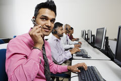 Young Service Operator Communicating On Headset Stock Photos