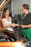 A young service worker in green overalls shaking hands with a be stock photography