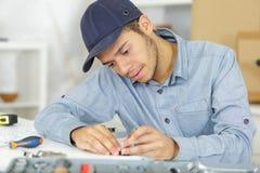 Young serviceman assembling parts. Serviceman royalty free stock photos
