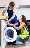 Young serviceman and smiling woman. Serviceman and unhappy girl standing near washing machine indoors. Focus on the woman Royalty Free Stock Photo