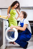 Young serviceman and smiling woman. Young serviceman and unhappy women standing near washing machine indoors. Focus on the man Stock Photo