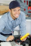 Young serviceman using multimeter. A young serviceman using multimeter stock images