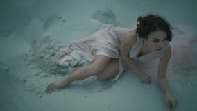 Young sexual brunette girl in light pink dress leaning on ground and touching her face while sitting on sandy shore stock footage