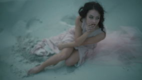 Young sexual brunette girl in light pink dress touching her face while sitting on sandy shore