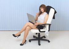 Young sexual girl - secretary sits in an armchair Stock Image