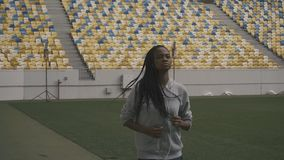 Young sexy african american fit woman listening music and jogging on the urban stadium background.  stock footage