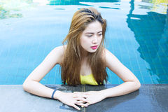 Young sexy asian woman posing in pool Royalty Free Stock Image