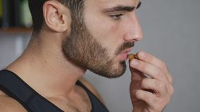 Young sexy athletic man eating almonds Stock Images