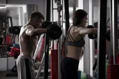 Young sexy athletic man and woman workout with dumbbells in gym Royalty Free Stock Photo