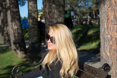 Young attractive business woman with long blonde hair in a park. Pigeon in the park, photographed from close. distance royalty free stock image