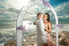 Young, sexy and attractive couple standing under arch during wed. Ding ceremony in tropical island. Dream wedding in exotic country, caribbean or Hawaii Royalty Free Stock Photos