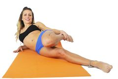 Young attractive fit woman at gym doing yoga exercise and stretching on mat in meditation and relax Stock Images