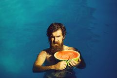 Man with watermelon and knife in pool. Young sexy bearded man with wet hair and beard swimming in pool with blue water holds knife and green red watermelon sunny royalty free stock images