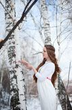 Young beautiful Slavic girl with long hair and Slavic ethnic attire posing in a spring forest near a birch tree with ritual bread Stock Images