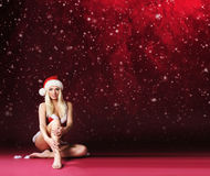 Young, sexy and beautiful female Santa on a Christmas background Royalty Free Stock Photos