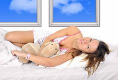 Young sexy  beautiful girl in nightgown lying on bed in bedroom hugging teddy bear smiling happy. Young sexy and beautiful woman in nightgown lying on bed at her Stock Image