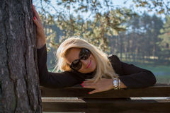 Young sexy beautiful girl in a park with long blond hair. Young sexy attractive business woman with long blonde hair in a park Royalty Free Stock Image
