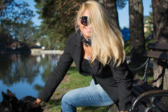 Young beautiful girl in a park with long blond hair. Young attractive business woman with long blonde hair in a park royalty free stock photography