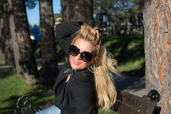 Young sexy beautiful girl in a park with long blond hair. Young sexy attractive business woman with long blonde hair in a park stock image