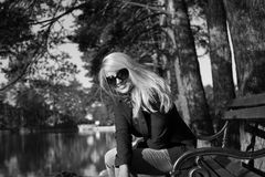 Young beautiful girl in a park with long blond hair. Young attractive business woman with long blonde hair in a park stock photography