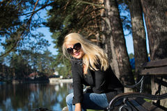 Young beautiful girl in a park with long blond hair. Young attractive business woman with long blonde hair in a park stock photos
