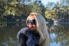 .Young beautiful girl in a park with long blond hair. Young attractive business woman with long blonde hair in a park royalty free stock photo