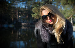 Young beautiful girl in a park with long blond hair. Young attractive business woman with long blonde hair in a park royalty free stock photos