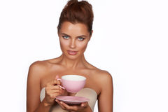 Young beautiful woman with dark hair picked up holding a ceramic cup and saucer pale pink drink tea or coffee on a white back Stock Photography