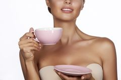 Young beautiful woman with dark hair picked up holding a ceramic cup and saucer pale pink drink tea or coffee on a white back Royalty Free Stock Image