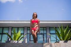 Young beautiful woman in pink bikini, posing on terrace of resort hotel, slim, tanned skin, fashion glamour Royalty Free Stock Photos